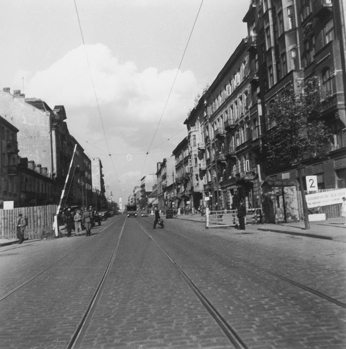 "Entrance number 2 to the Warsaw ghetto guarded by German soldiers and policemen.  Joest's original caption reads: ""In front of the gates to the Ghetto there are always Polish policemen and a Wehrmacht sentry to whom Poles are required to show their identification papers.  Right behind the gates were vendors, even children, who tried to sell their trifles."""