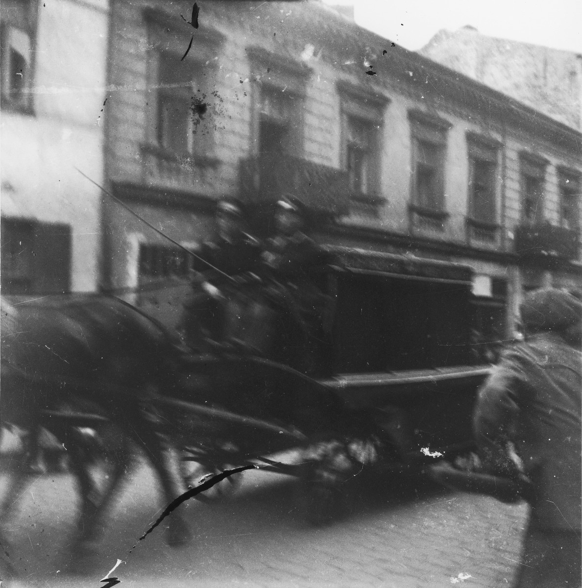 """Undertakers drive a horse-drawn funeral wagon through the streets of the Warsaw ghetto.   Joest's original caption reads: """"Everywhere in the Ghetto I photographed these black hearses which I later followed to the Jewish cemetery."""""""