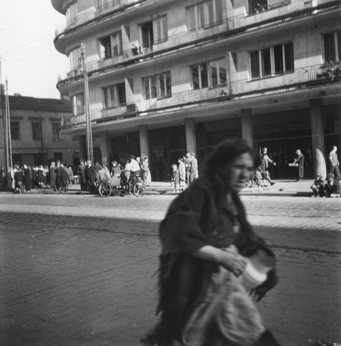 """A woman walking down the street carrying a milkcan  in the Warsaw ghetto.  Joest's original caption reads: """"An old woman with an empty jug - was she fetching milk?  Was there still milk?  In the background to the right of her on the other side of the street, a German soldier, rifle over his shoulder, taking stiff, booted steps."""""""
