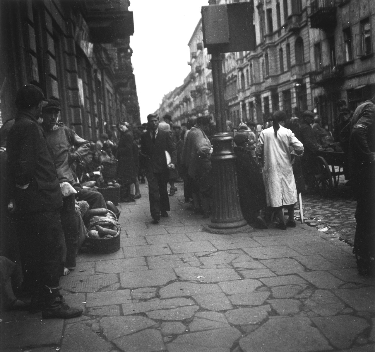 "Vendors selling bread on the street in the Warsaw ghetto.  Joest's original caption reads: ""I don't know where this was.  Fresh bread was sold on the street, but it was seldom that anyone bought anything.  A few steps further on and children were starving on the pavement."""