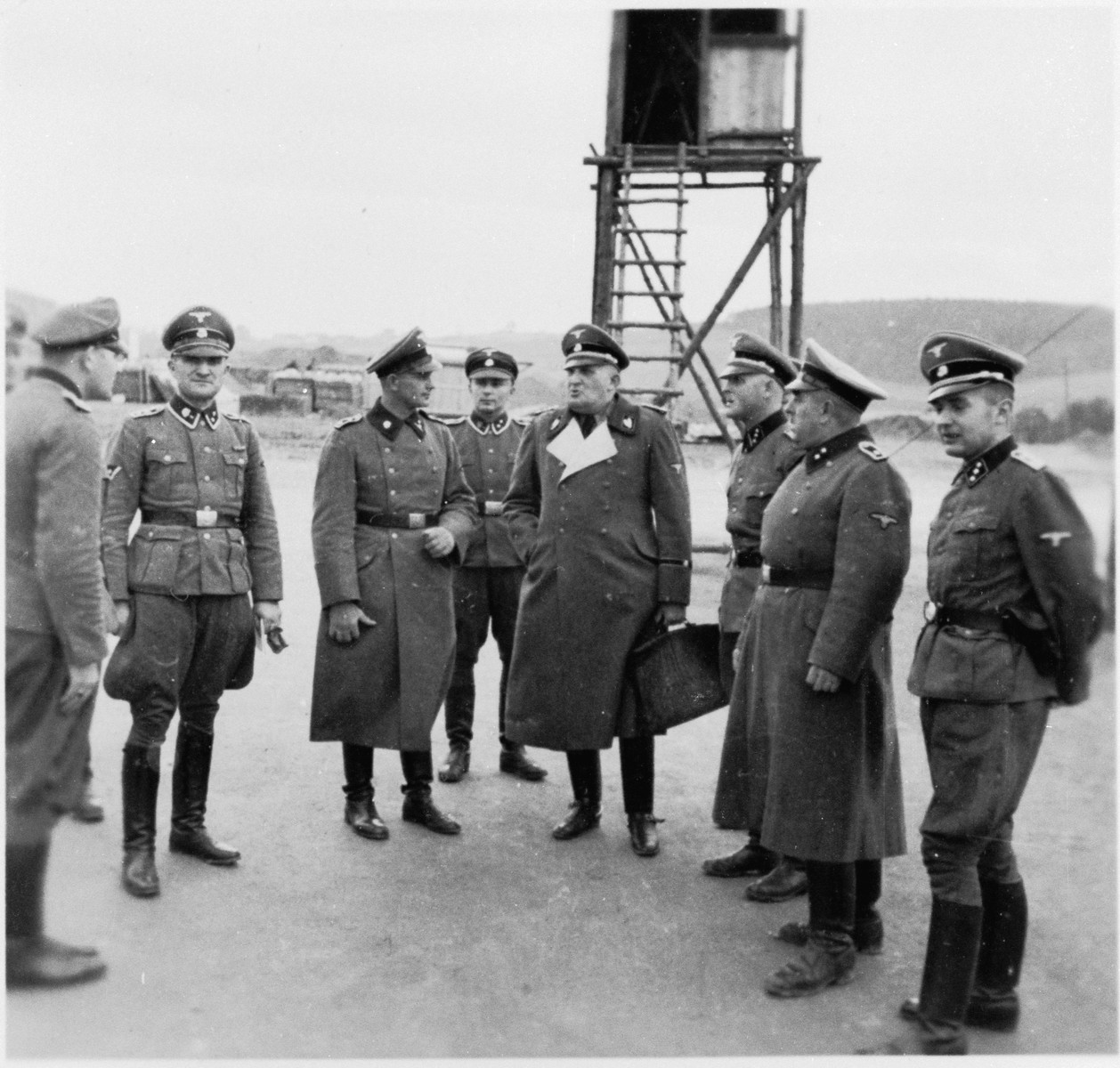 SS-Brigadefuhrer Richard Gluecks, the Inspector of Concentration Camps, stands carrying a briefcase with other SS men on an official visit to Gross-Rosen.  This was probably taken shortly before Gross-Rosen became an independent concentration camp.  Prior to May 1, 1944 it was a sub-camp of Sachsenhausen.