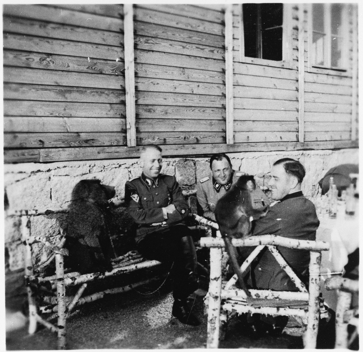 SS officers sit outside a building at the Gross-Rosen concentration camp laughing with a dog and a monkey.