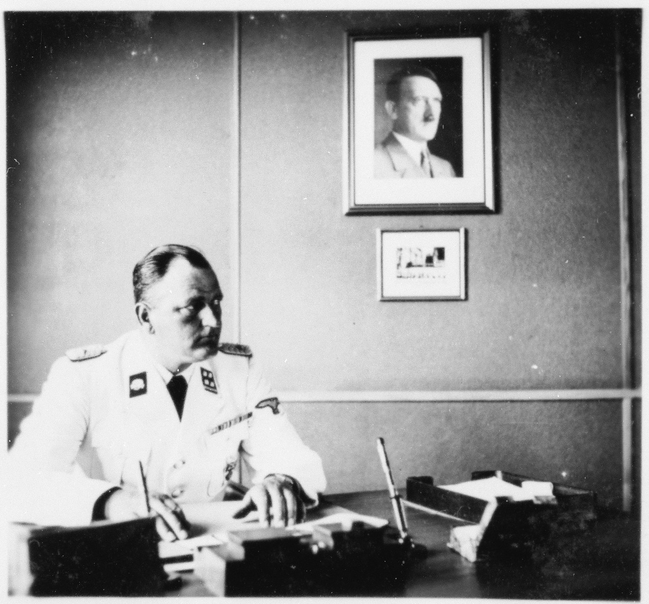 The commander of Gross-Rosen, SS-Obersturmbannfuehrer Arthur Roedl sits at his desk in his office with a photograph of Adolf Hitler hanging on the wall.
