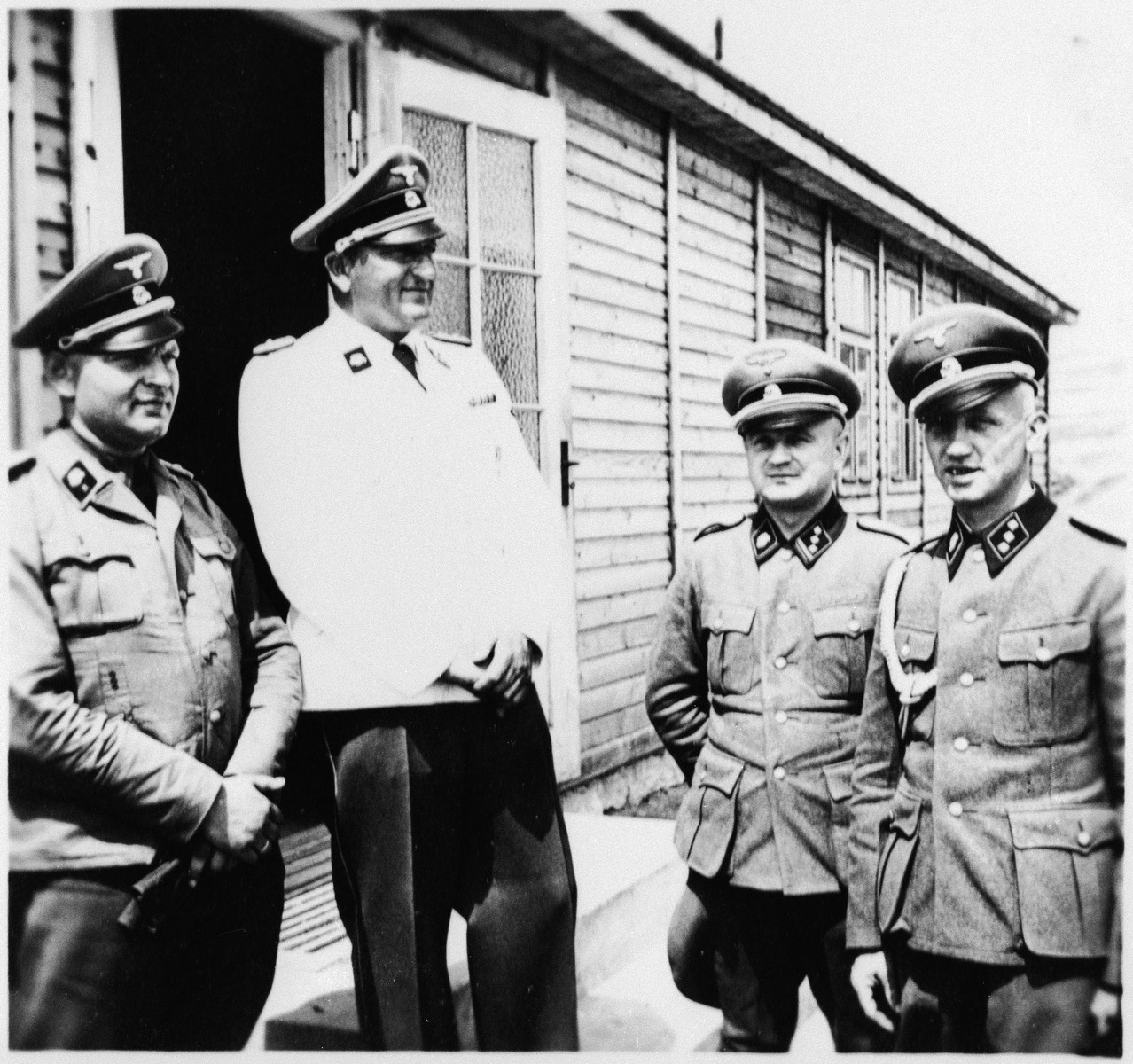 Four SS men stand outside a building in the Gross Rosen concentration camp.  The commandant Arthur Roedl is second from the left.  His adjutant, Kuno Schramm is pictured on the right.  On the left is probably Hermann Michl, head of administration.