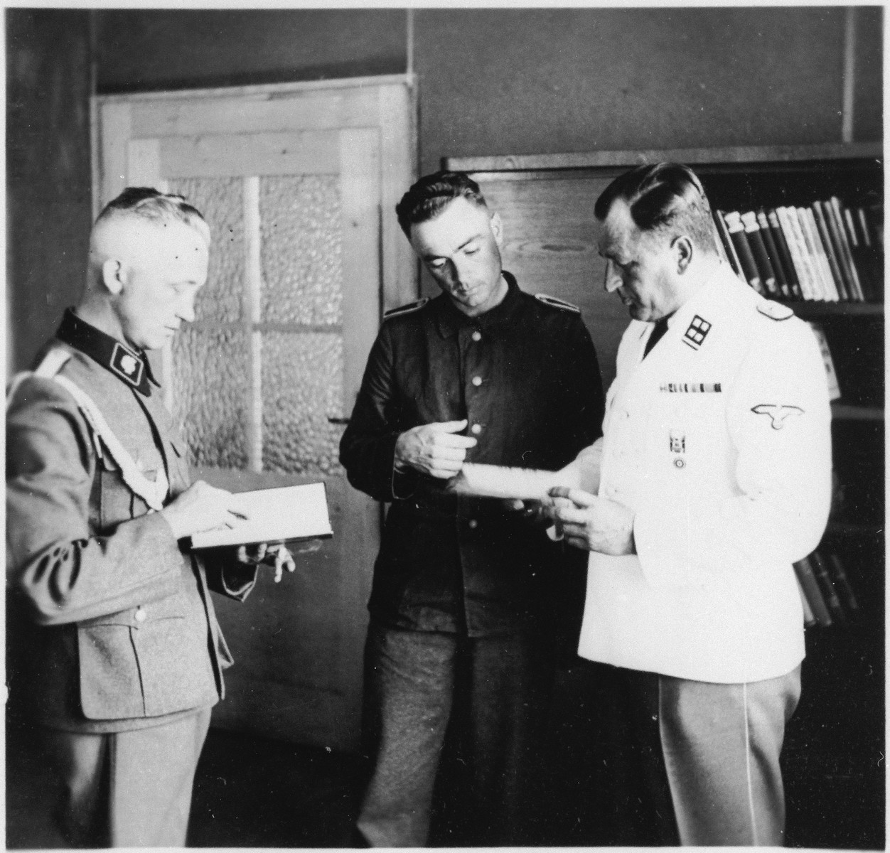 The commander of Gross-Rosen, SS-Obersturmbannfuehrer Arthur Roedl reads from book in the company of two other SS men in his office.  Pictured on the right is his adjutant Untersturmfuehrer Kuno Schramm.