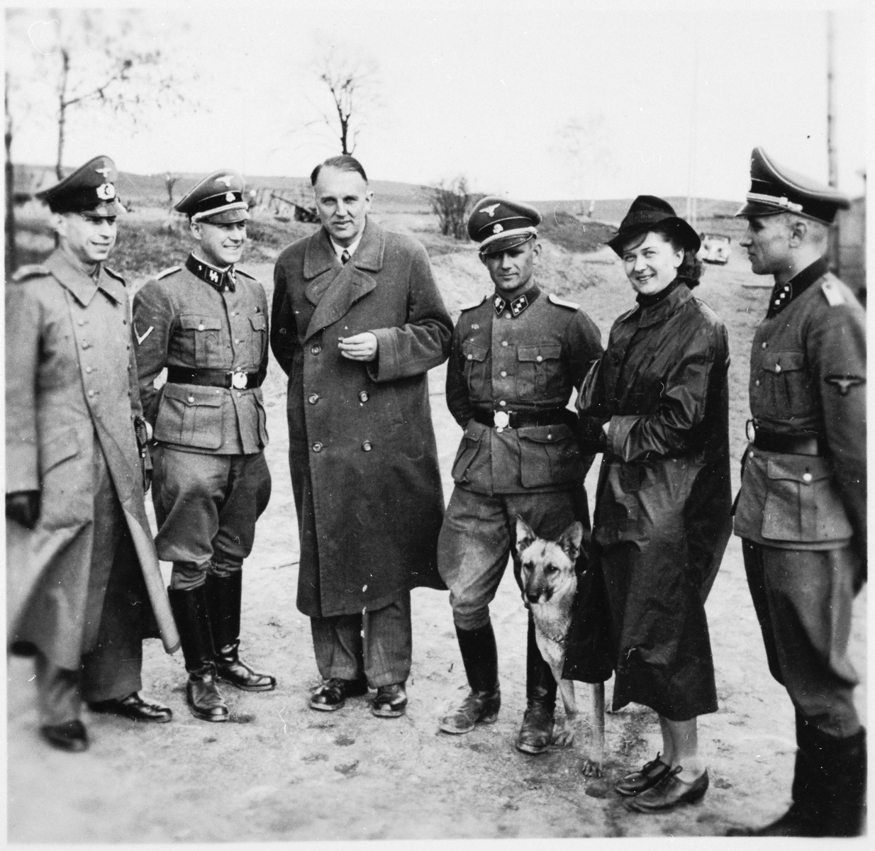 A group of SS officers, a woman and a dog stand on the grounds of the Gross-Rosen concentration camp.  Anton Thumann is pictured third from the right.
