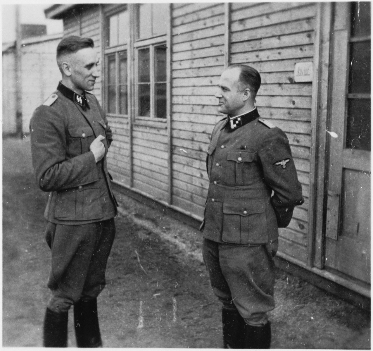 Two SS officers stand and talk outside of a building at the Gross-Rosen concentration camp.  Pictured on the left is probably the camp physician, Dr. Friedrich Entress.