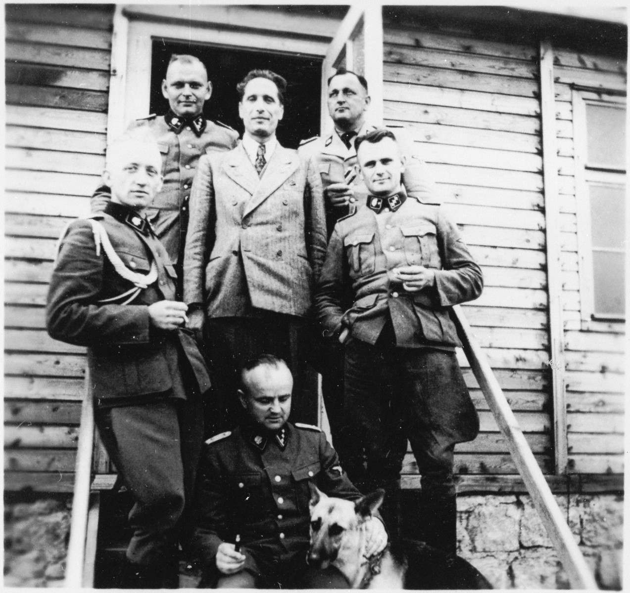 A group of SS officers stand on the steps of a building at the Gross-Rosen concentration camp.  Standing on the far left is the adjutant, Kuno Schramm.  Michl is standing behind him on the top left.  The Commandant Arthur Roedl is on the top right.  Beneath him is including Anton Thumann (bottom right).