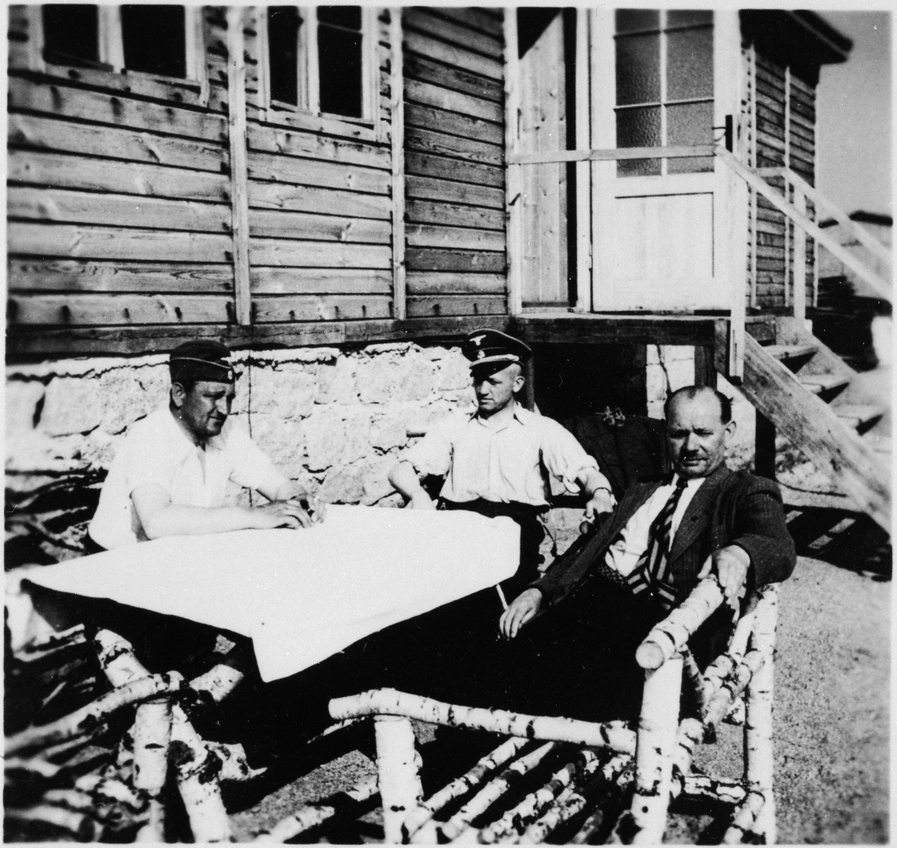 SS officers and an unidentified man sit at a picnic table outside a building at the Gross-Rosen concentration camp.  Pictured on the left is the commandant, Arthur Roedel.  His adjutant, Kuno Schramm is in the center.