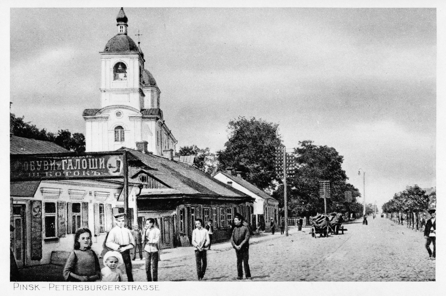 "View of a street in prewar Pinsk with signs in Russian.  The original German caption reads ""Pinsk -- Petersburgerstrasse""."