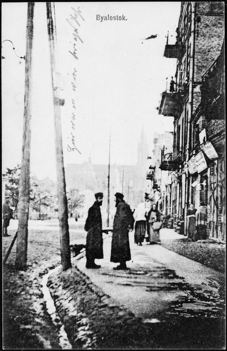 Jewish men stand on a commercial street of prewar Bialystok.