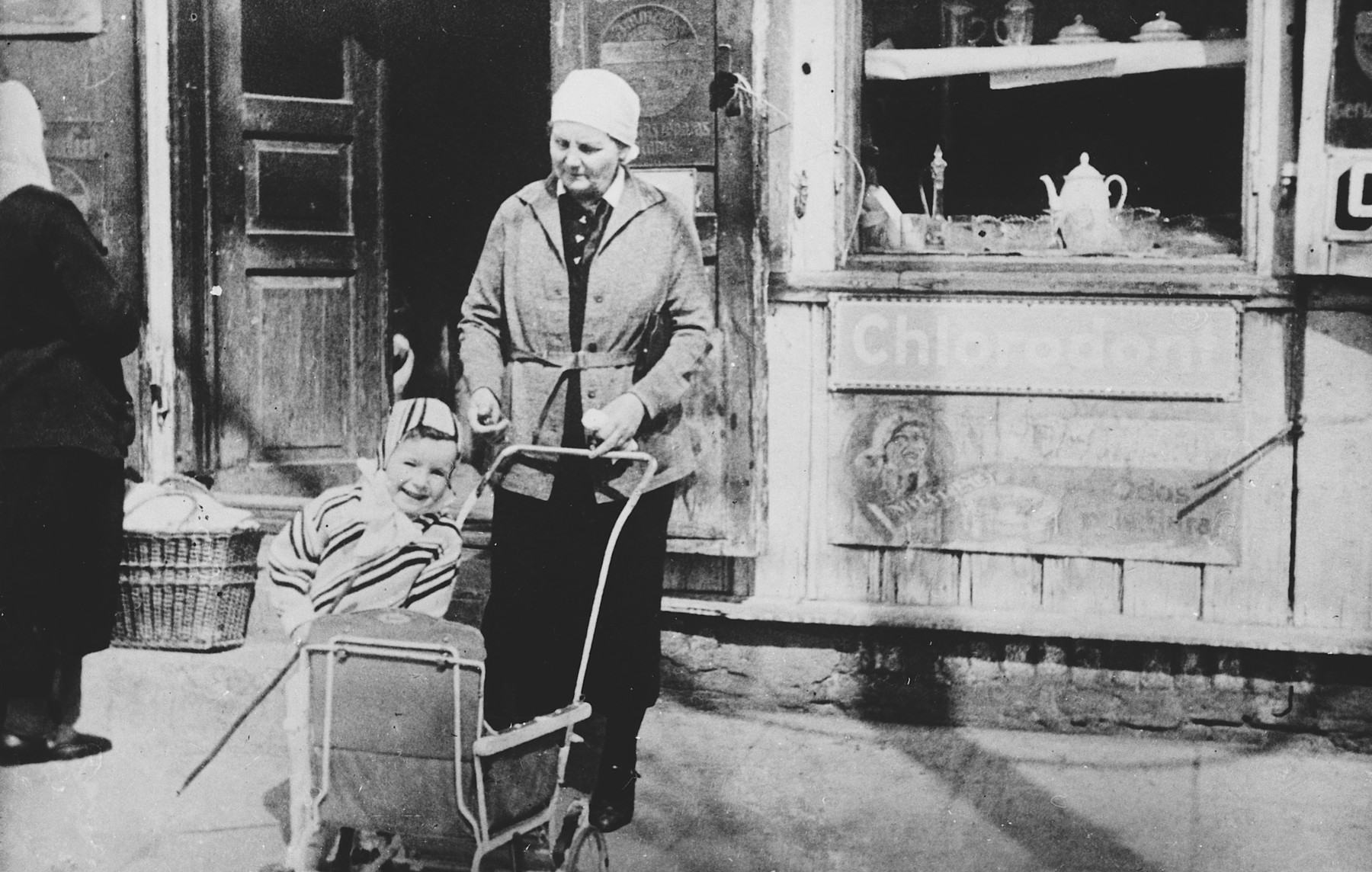A Jewish toddler stands next to his stroller alongside his Lithuanian nanny.  Pictured is Alik Shtromas and his nanny, Vera.
