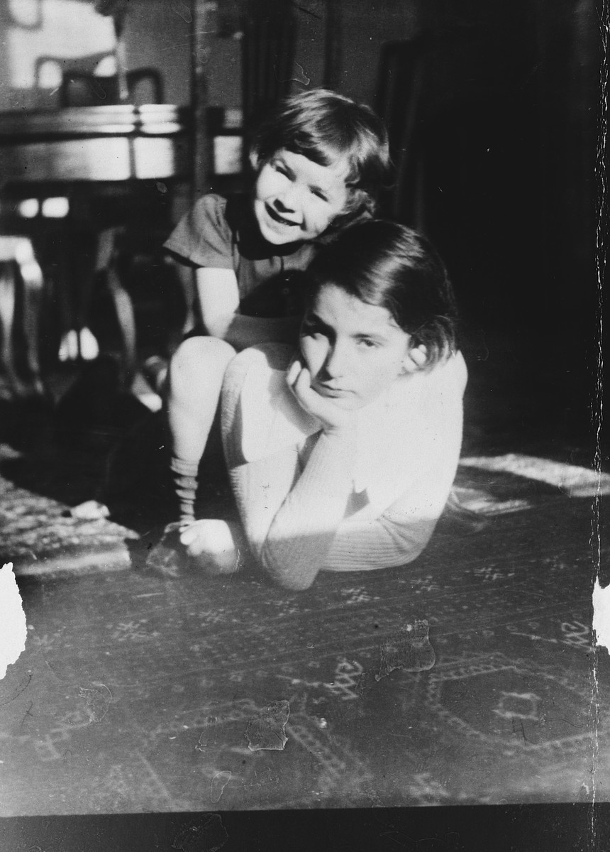A Lithuanian-Jewish toddler sits on the back of his older sister in their living room.  Pictured are Alik and Margarita Shtromas.