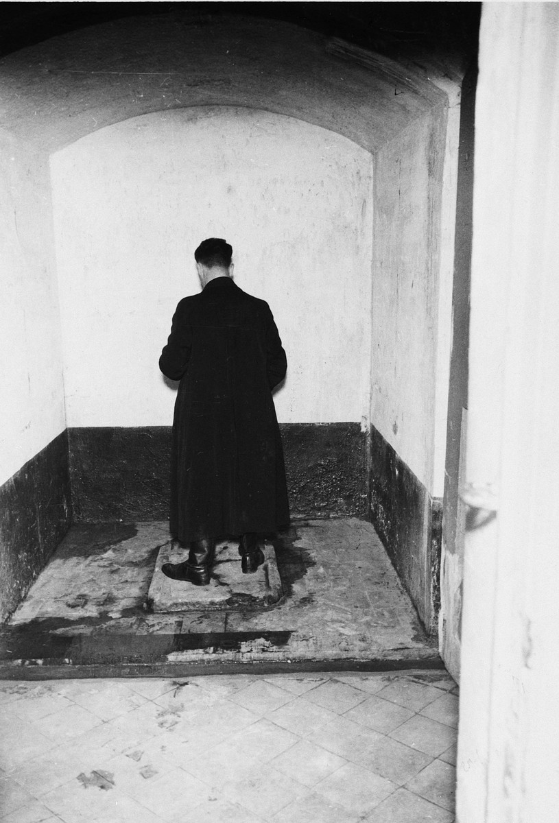 "A survivor reenacts the treatment of prisoners in a torture chamber in the Breendonck concentration camp.  Original caption reads, ""It is alleged that prisoners were made to stand facing the wall in the manner shown above and that (a) wooden bullets were fired at them (b) cold water and steam or boiling water was thrown at them. No proof of this is forthcoming although there are many small marks on the wall.  No cognizance has been taken of the above stories."""