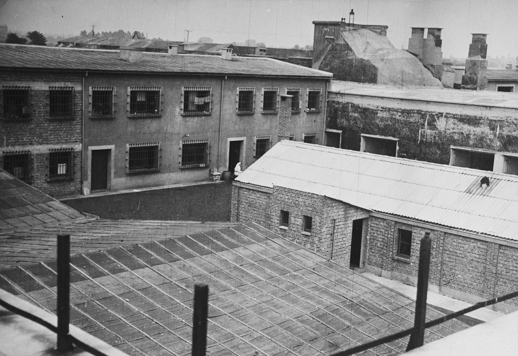 "Aerial view of the infirmary in the Breendonck concentration camp.  The original caption reads ""The building with the corrugated roof is the infirmary.  Prisoners reporting sick were kept waiting in this yard for anything up to three hours whether it was winter or summer.  They had to stand during the whole of this time completely naked.  The medical examination never lasted more than two minutes."""