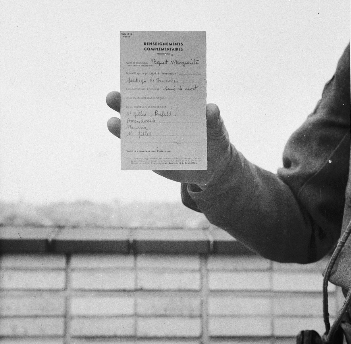 Mme. Margueritte Paquet shows a warrant for her execution issued in the Breendonck internment camp.