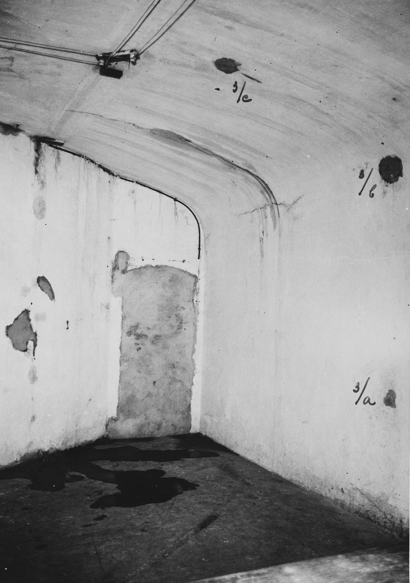 "Interior view of a torture chamber in the Breendonck concentration camp.  Original caption reads, ""The marks on the wall and roof indicate where a pulley used to be.  Prisoners were strung up  to the roof by means of a pulley -- sometimes feet-first, sometimes head-first.  The pulley was dismantled by the Germans in August 1944."""