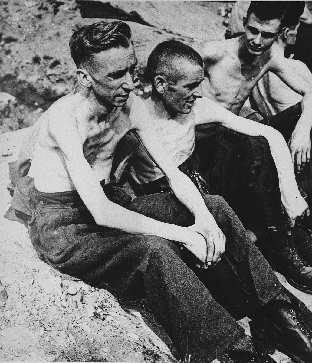 Three malnourished British POWs sit on the grounds of Stalag XIB [Eleven B], a camp outside Fallingbostel.  Pictured is Pte. W. Buchanan of Glasgow.