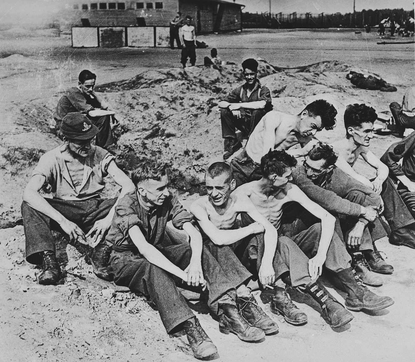 """Newly liberated British POWs sit on the grounds of Stalag XIB [Eleven B], a camp outside Fallingbostel.  The original caption reads, """"On April 16th the first Prisoner of War Camp containing British prisoners was liberated by advancing tanks of the British Armoured Brigade.  The camp is Stalag 11B  just south of Fallingbostel, which is about 10 miles southwest of Soltau.""""  The liberated prisoner at the back left is probably  Vincent J. Riccio, an American POW and Technical Sergeant ,flight engineer/gunner in the US Army Air Corps.  After his airplane was disabled, he was sent to Stalag Luft IV and then taken on a forced march to Fallingbostel where British prisoners helped care for him."""