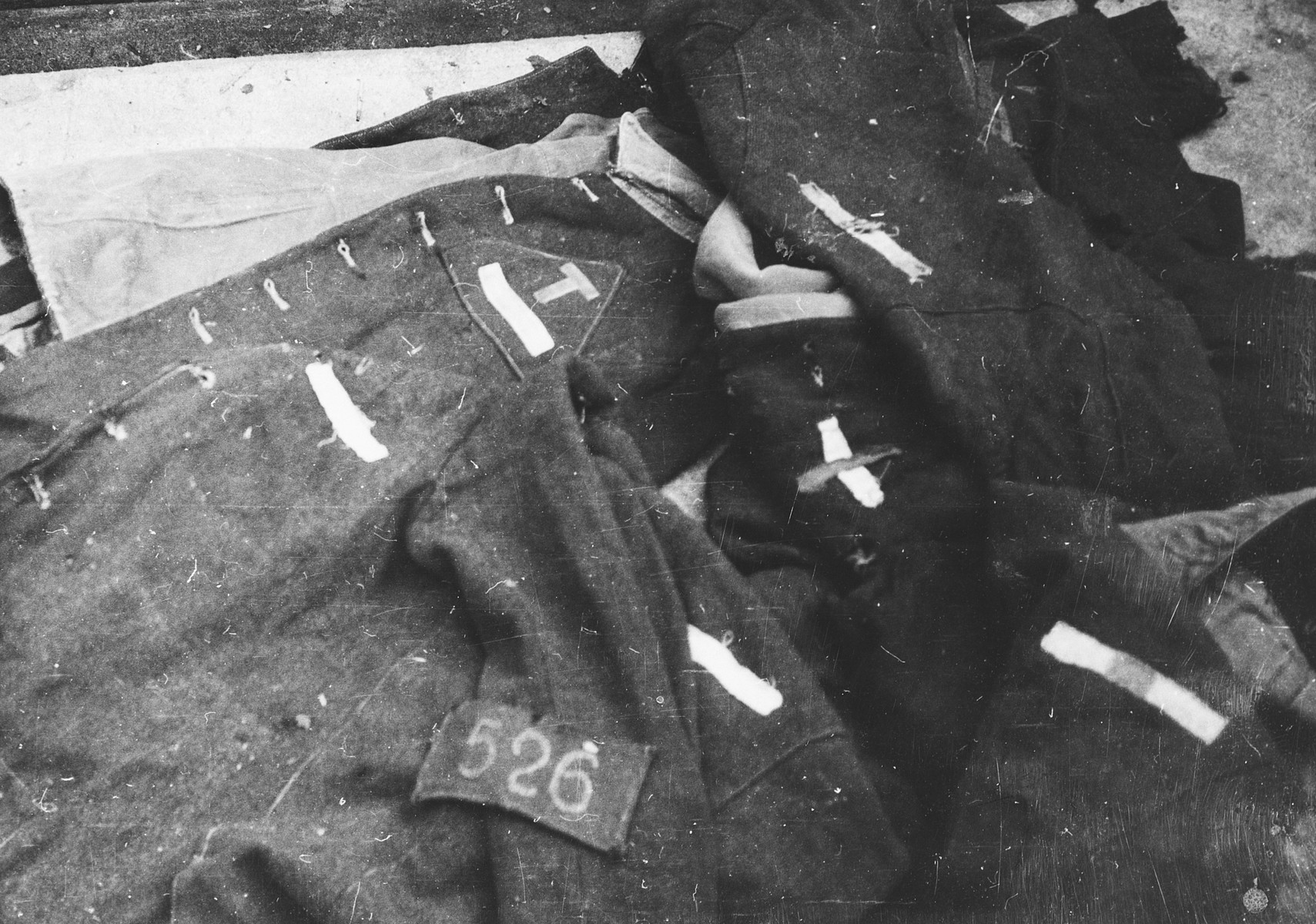 A pile of uniforms with distinctive badges discovered in the Breendonck concentration camp.