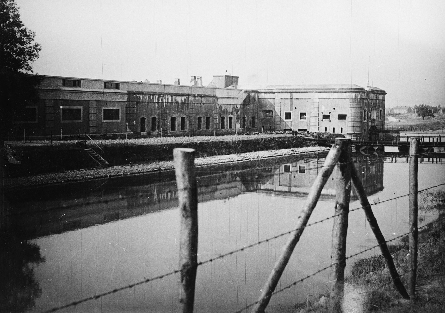 View of the moat and barbed wire fence surrounding the Breendonck concentration camp.