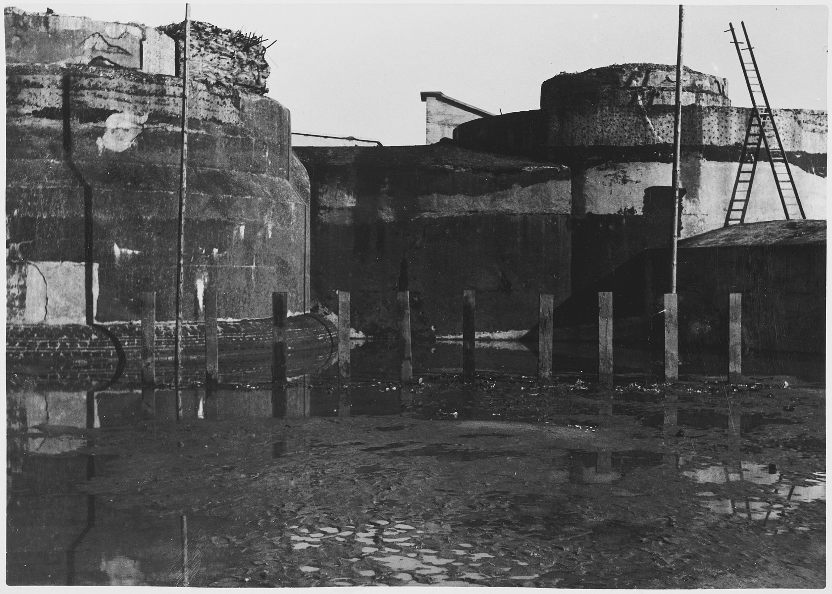 "View of the execution site in the Breendonck concentration camp.  The original caption reads, ""The place where prisoners were shot.  Before being shot, the prisoners had to erect the sleepers.  The sleepers shown on the photograph are not those used by the Germans but have been erected by the Belgians to show what the execution yard looked like."""
