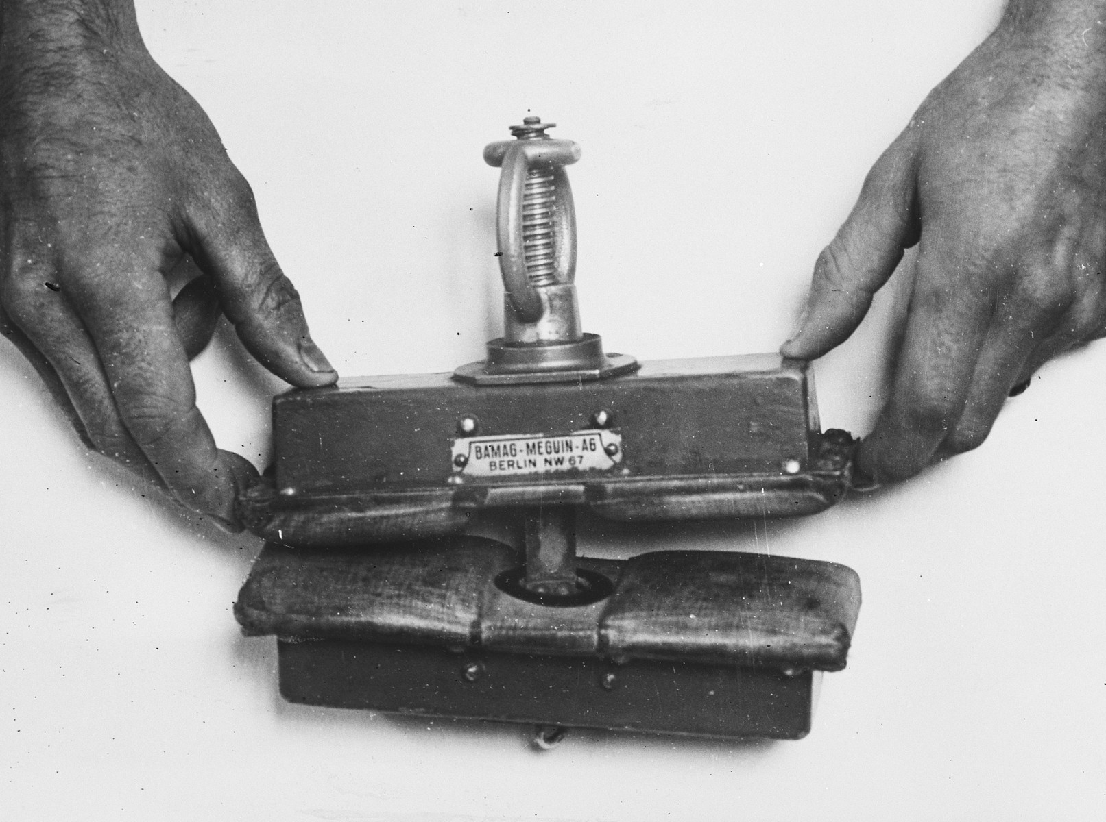"Demonstation of an instrument used to crush fingers in the Breendonck concentration camp.  The original caption reads, ""The above photograph shows an instrument which the Germans used as a finger-press.  It was discovered at the German Soldatenheim, 47 Chausee de Mons, SOIGNIES by Mlle Rosette Christieans.  The instrument was shown to Madame Pacquet who had her fingers crushed until her nails came off.  She identified it as identical with the instrument which the Germans had used to torture her in Breendonk. The moment she saw it she said, ""Take it away.  I never want to see it again."""