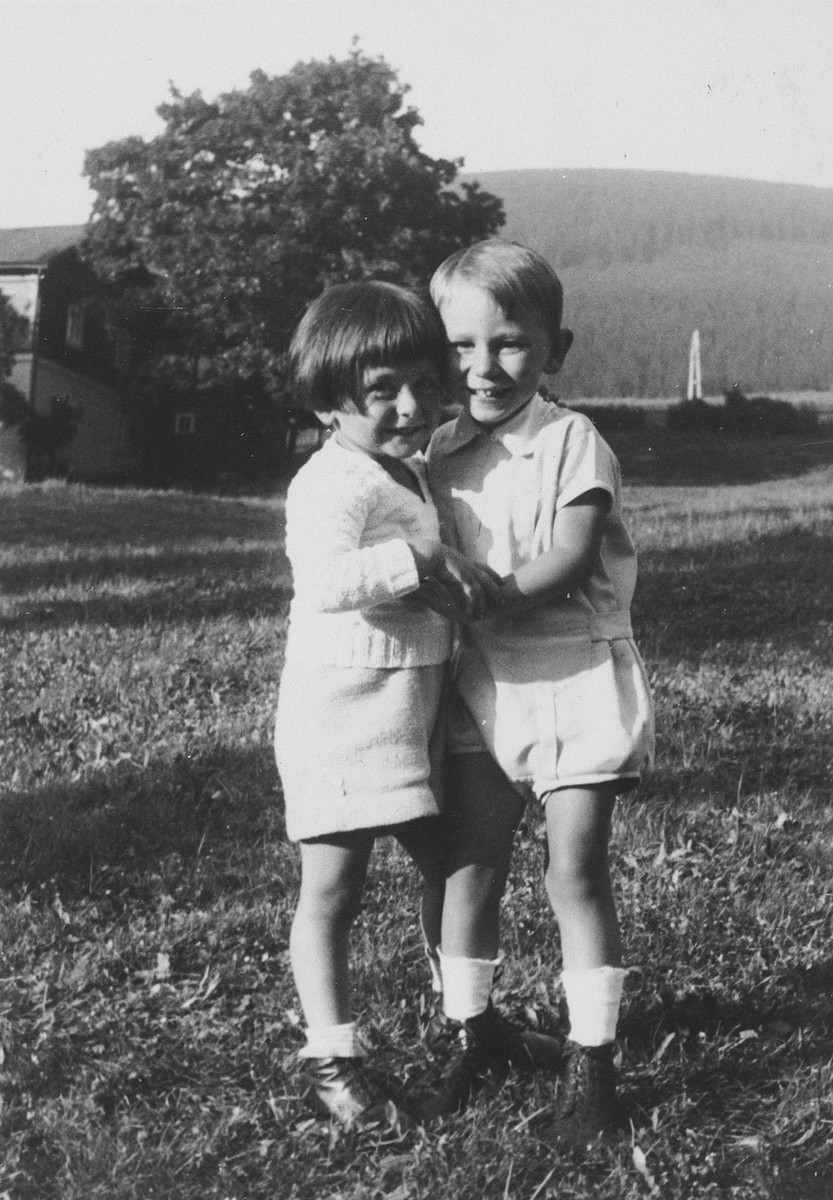 Two young children pose together on a grassy field.  Pictured on the left is Michael Grunbaum.