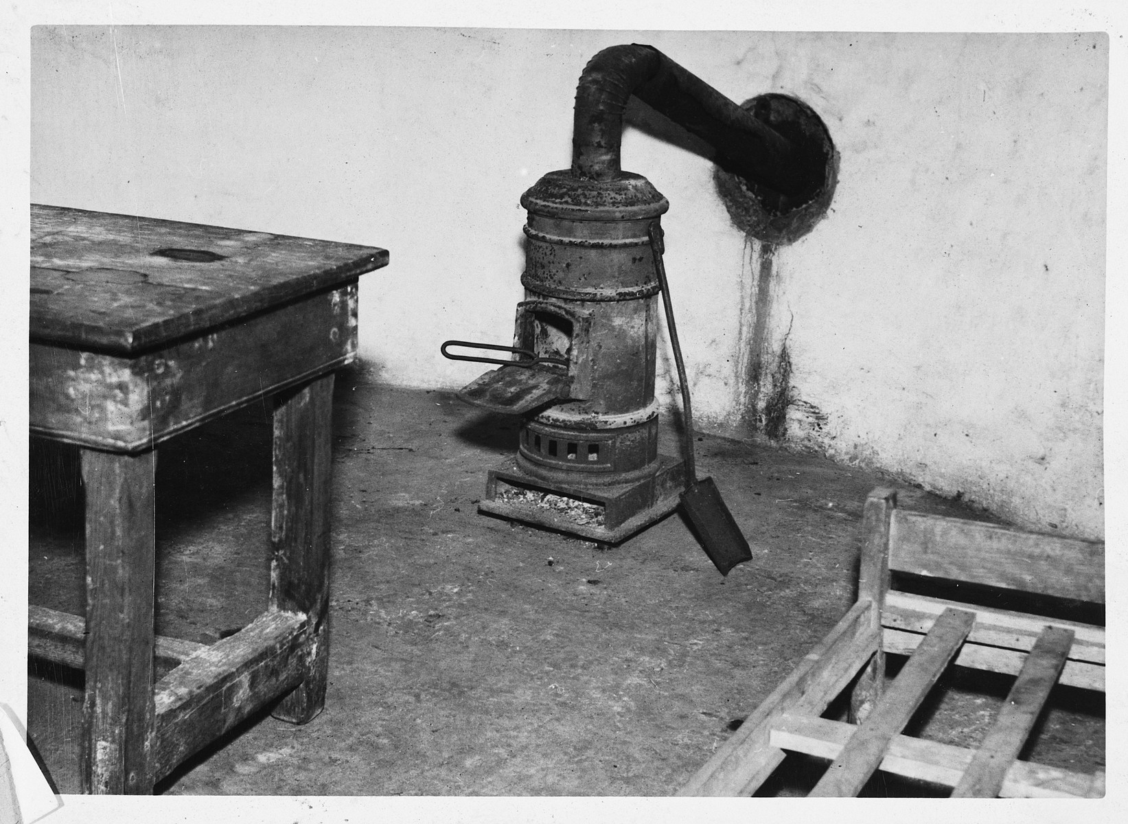 """Interior view of a torture chamber in the Breendonck concentration camp.  The original caption reads """"Stove, table and bed in the torture chamber.  The prisoners were beaten on the table.  Pokers were heated in the stove."""""""