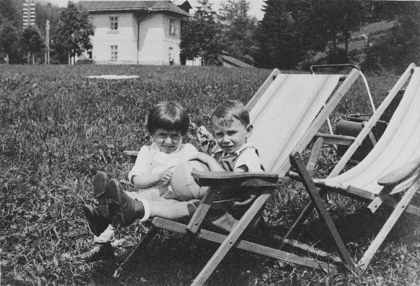 Two young children sit next to each other on canvas lawn chairs on a grassy field.  Pictured on the left is Misa Grunbaum.