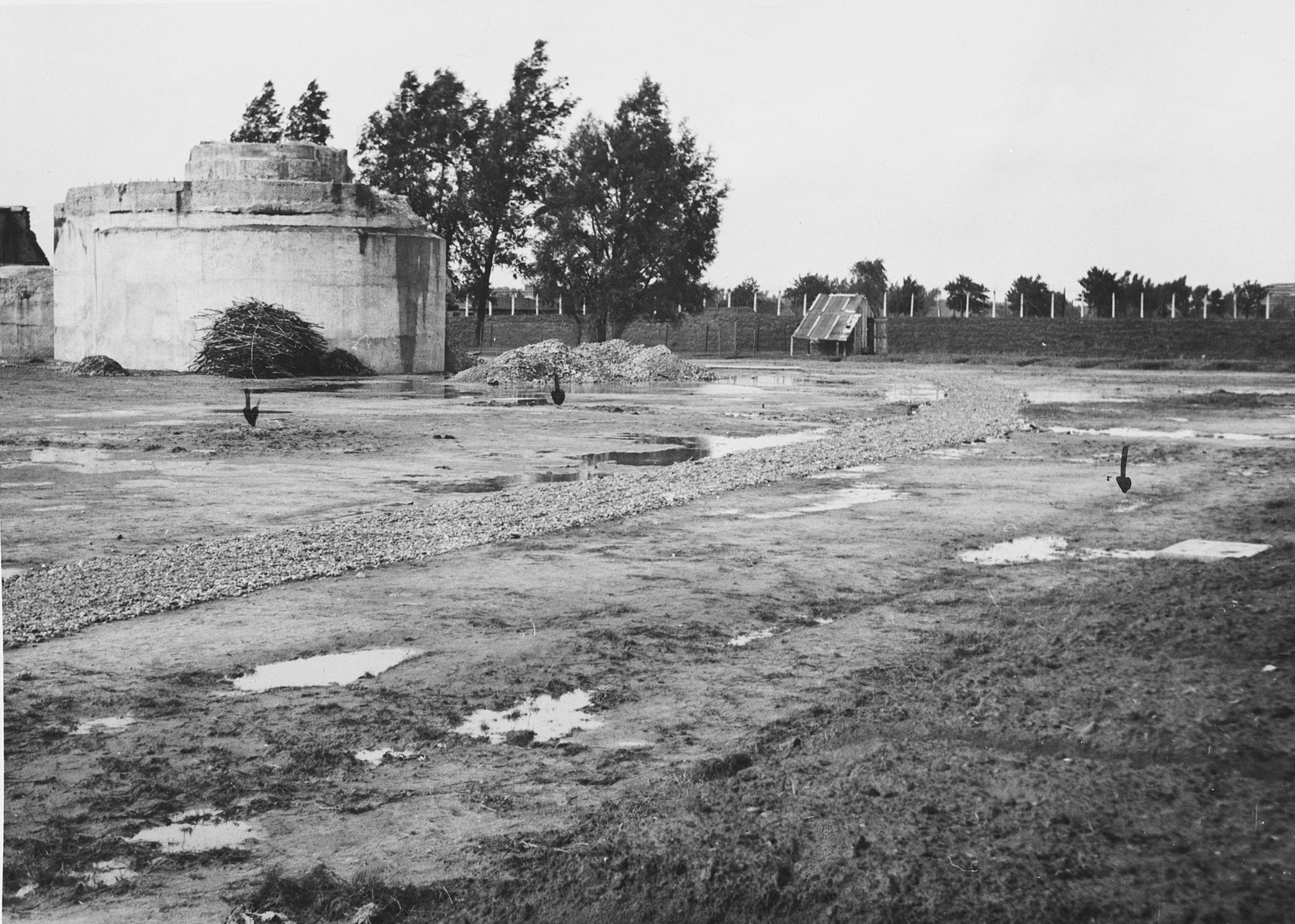 "View of the prison yard in the Breendonck concentration camp.  The orginal caption reads, ""The red arrows indicate soft earth which has been dug up to find whether or not any bodies were buried there.  Nothing was found."""