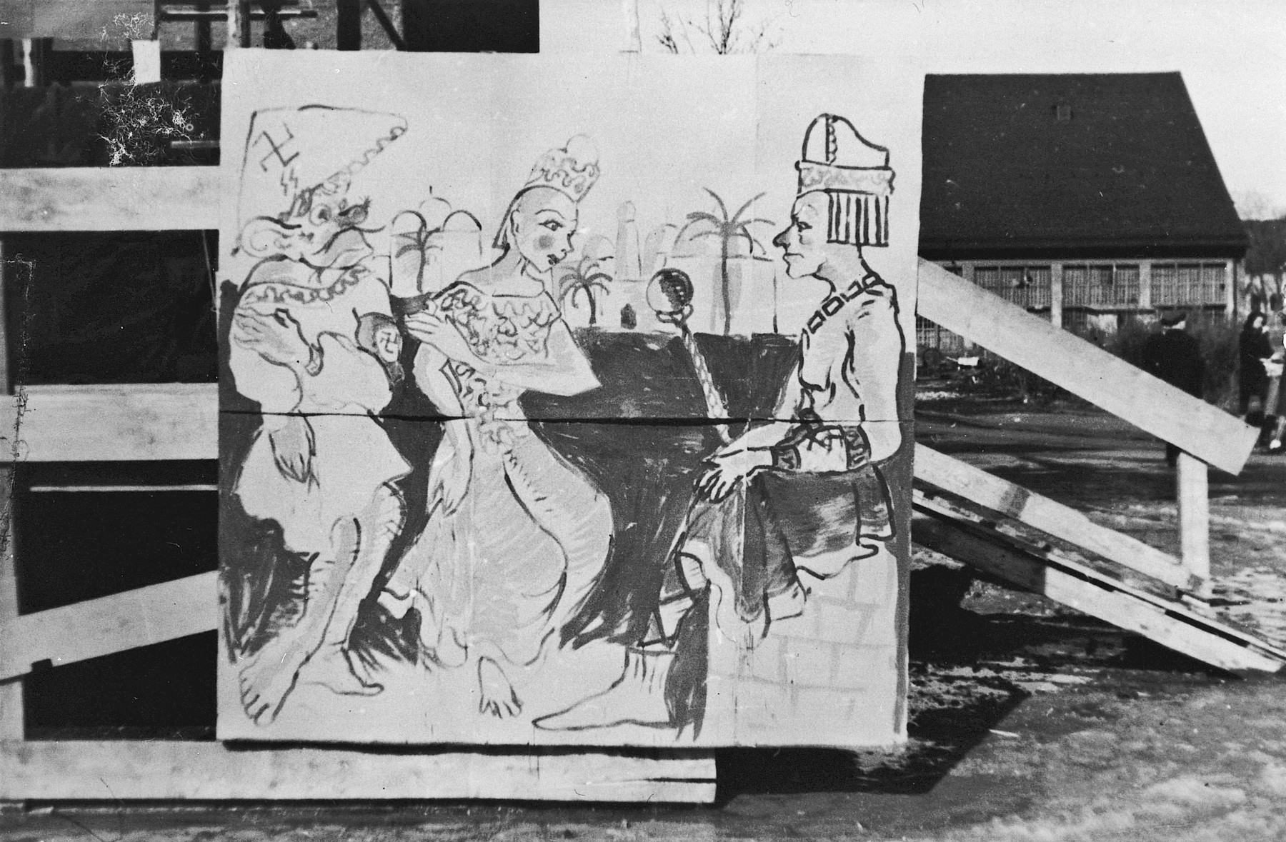Photograph of a large poster in the Landsberg DP camp displayed during a Purim celebration showing a scene from the Purim story, only with the villain Haman wearing a hat with a swastika and a Nazi armband.