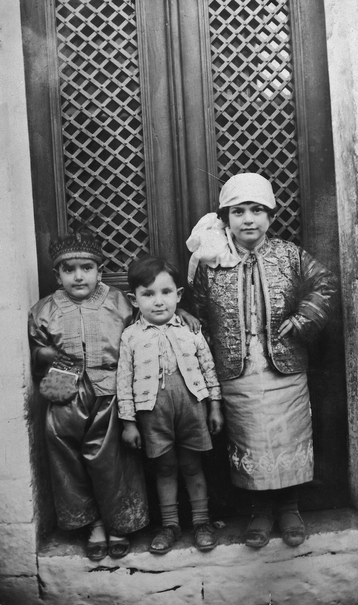 Three young Greek Jewish children pose in front of their home in their Purim costumes.  Pictured in the center is Michael Matsas along with two of his cousins.
