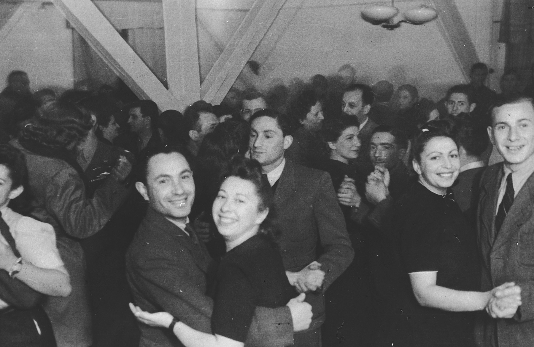 Couples in the Landsberg DP camp dance in a large public hall.