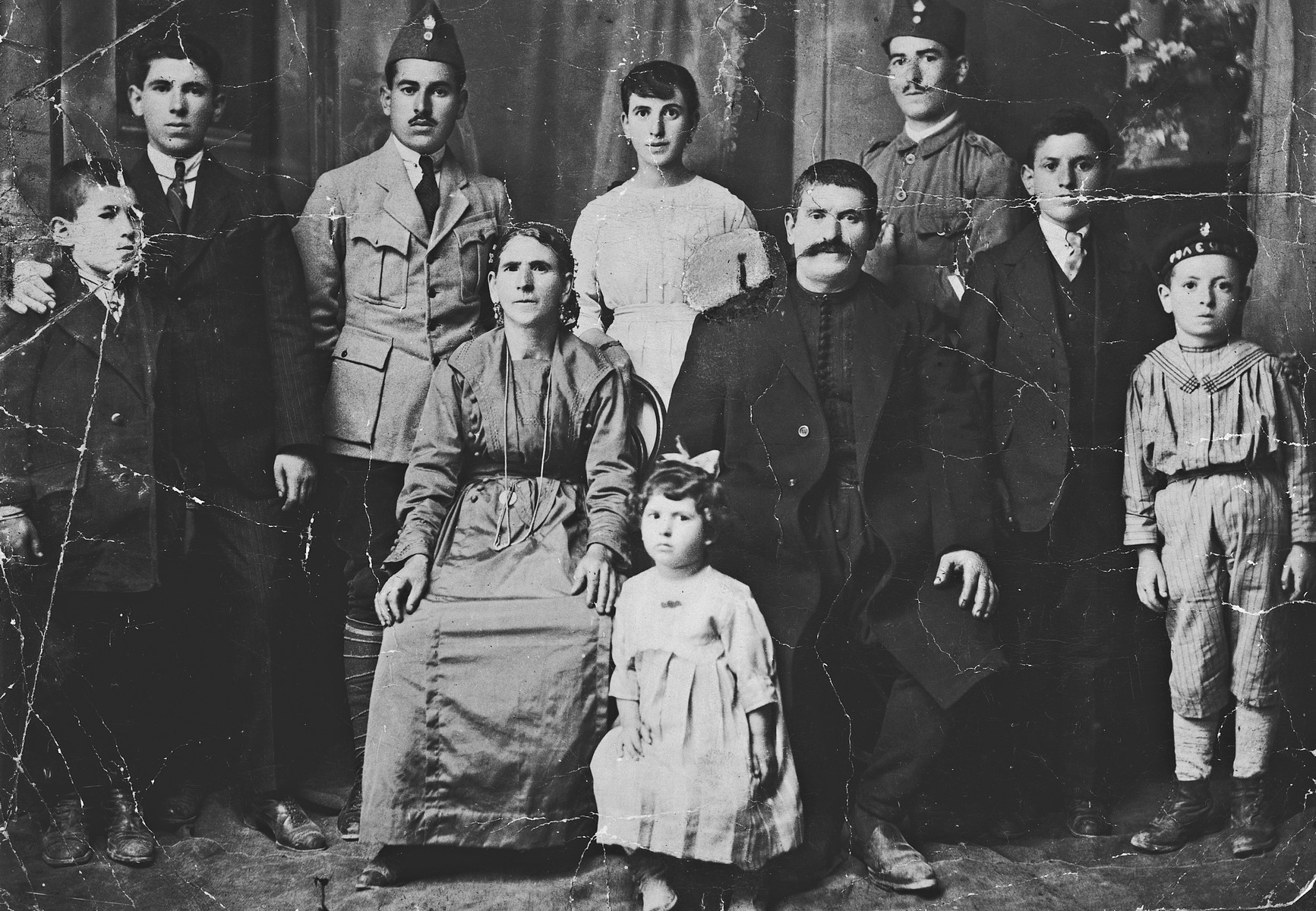 Studio portrait of a large family of Greek Jews from Ioannina discovered crumpled on the floor of their ransacked home after the war.  Pictured are members of the Matsas family.  Seated are Sarina and Nahoum Matsas and Rebecca (b. 1916).  Standing from left to right Eliasaf (b. 1910), Leon (b. 1902), Raphael (b. 1899), Rosina (b. 1904), Jeshua (b. 1896), Elias (b. 1907) and Michael (b.1912).