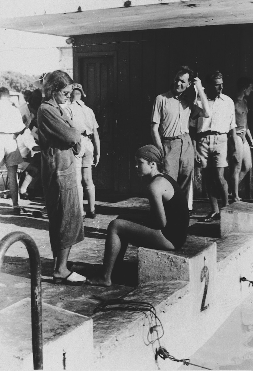 An Austrian-Jewish swim champion sits by the pool at Bat Galim shortly after her arrival in Palestine.  Pictured in the bathing suit is either Hanni or Judith Deutsch.
