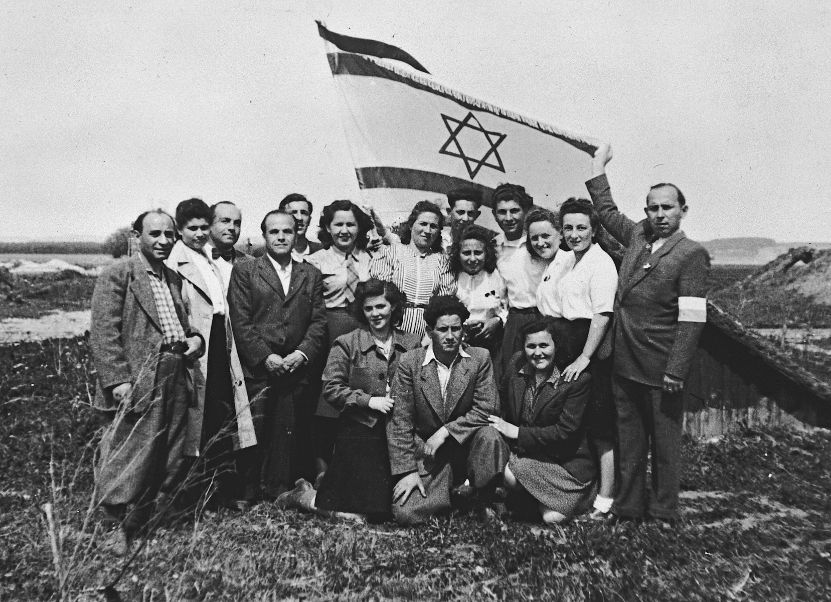 Jewish displaced persons n the Landsberg camp gather for a group portrait underneath a large Israeli flag.  Among those pictured are Max Freidberg (third from left) and Rachel Freidberg (sixth from left in a white blouse and tie).