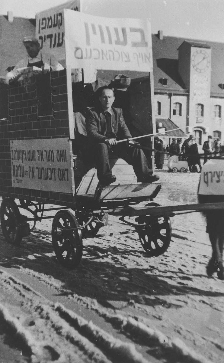 A Jewish DP drives a horse drawn float through Landsberg decorated with signs denouncing Ernest Bevin and calling for greater immigration to Palestine.