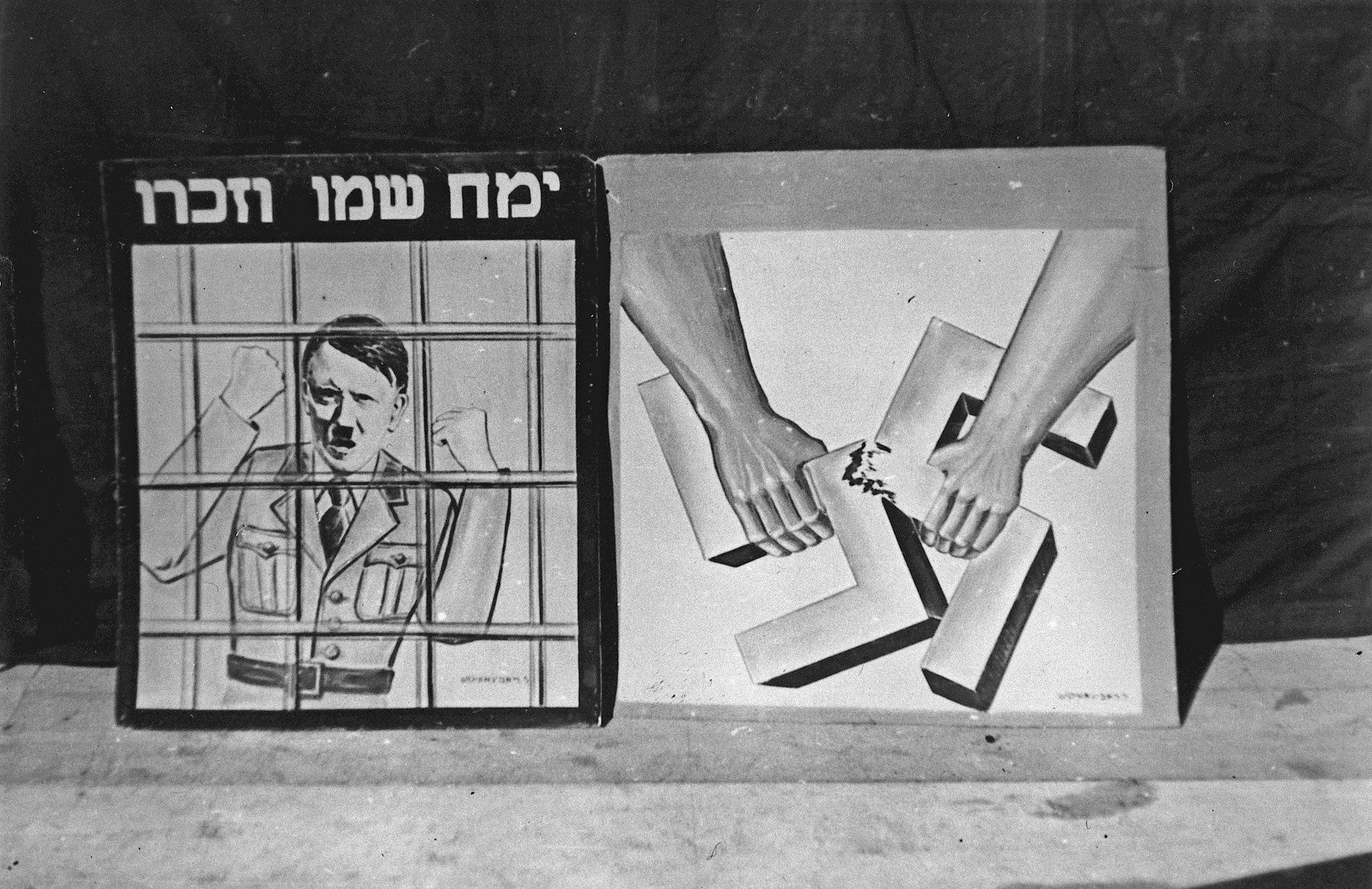 """Photograph of two posters in the Landsberg DP camp displayed in what is probably a Purim celebration.  The first shows a picture of Hitler ranting behind bars.  The caption reads, """"May his name and memory be wiped out.""""  The second shows two strong arms breaking apart a swastika."""