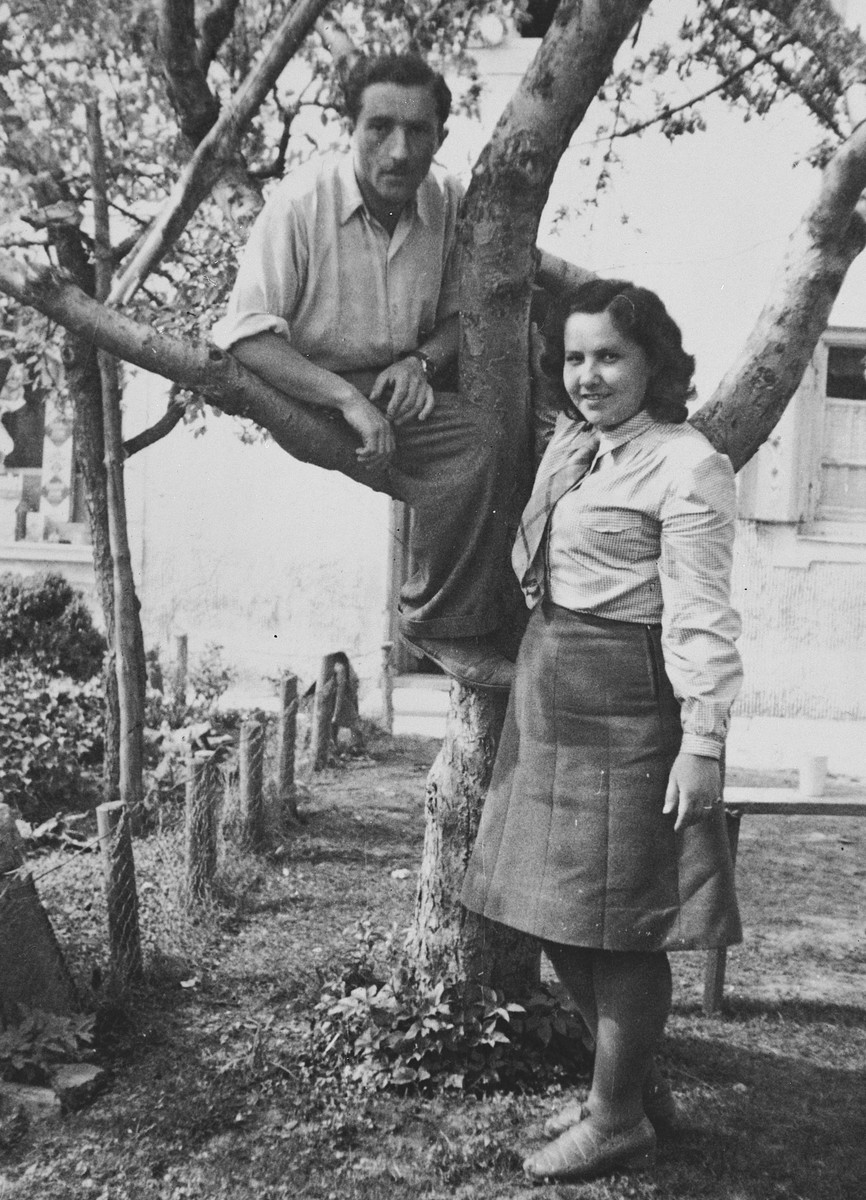 A young Jewish couple poses by a tree in the Landsberg DP camp.  Pictured are Rachel and Izaac Friedman.
