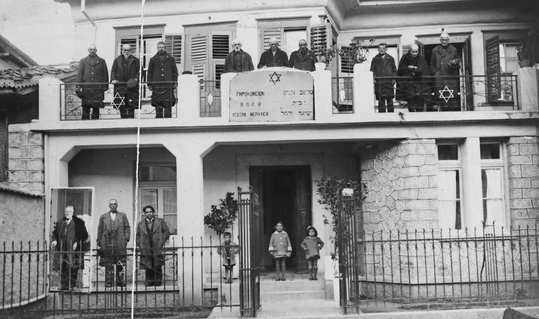 A group of Greek-Jews poses on the balcony and in front of the main entrance to the Beit Yeshua veRahel Hebrew Home for the Aged in Ioannina.