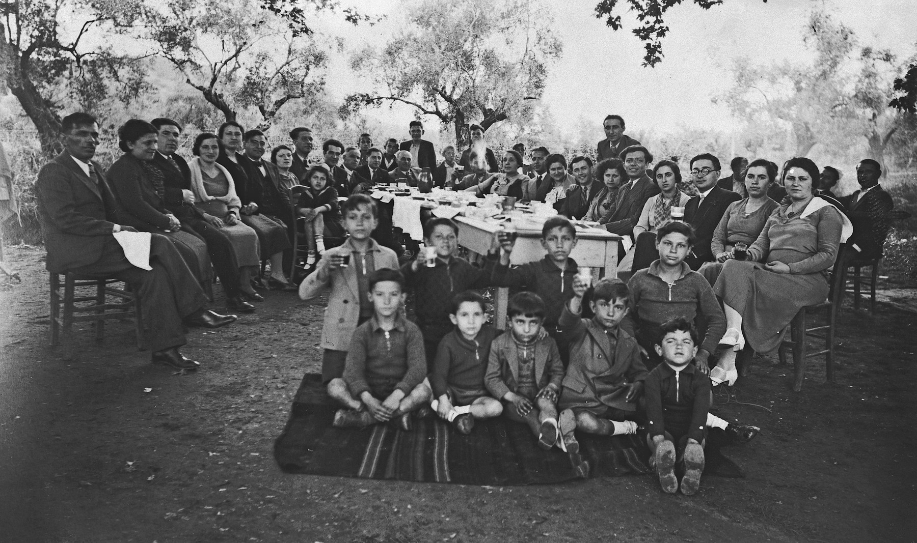 Employees and family of the National Bank of Greece in Arta gather for a group portrait during an outdoor celebration.  Michael Matsas is seated in the front, second from the left.  His parents, Leon and Esther Matsas, are seated behind him, third and fourth from the left.