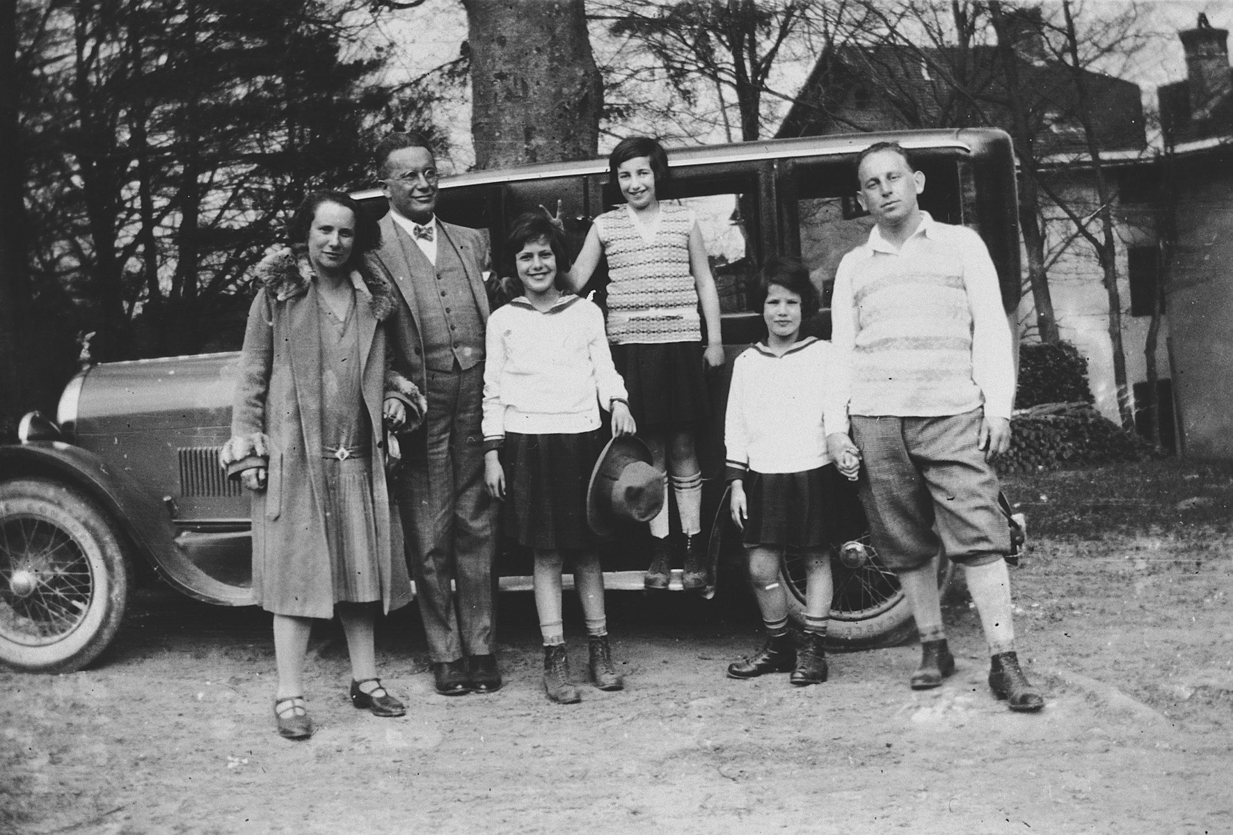 An Austrian Jewish family poses in front of a large automobile.  From left to right are Rachel Deutsch, Max, Judith Deutsch, Boli, Hanni Deutsch and Amiel.