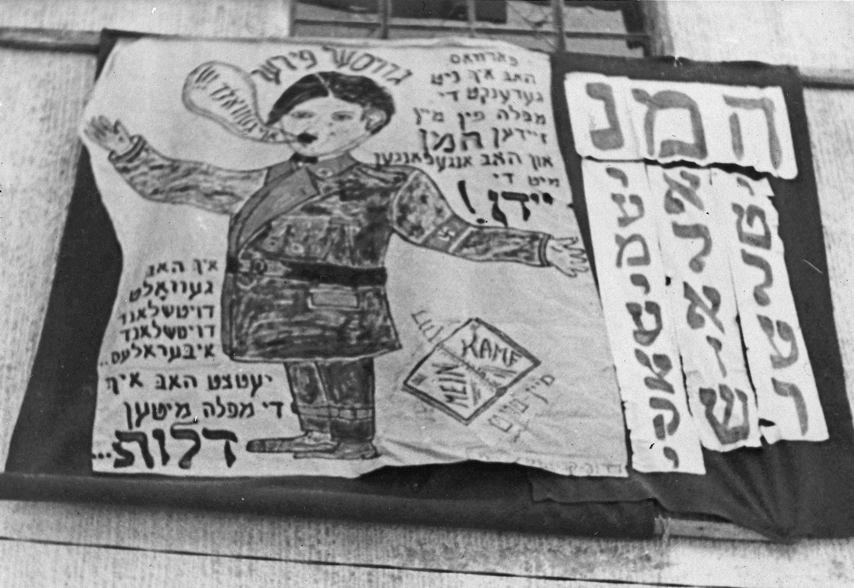 """Photograph of a banner in the Landsberg DP camp with a cartoon illustration of Hitler hung during a celebration of the Purim holiday.  Tha caption reads """"Why didn't I remember the downfall of my grandfather Haman and not get involved with the Jews?""""  There is then a short rhyme that translates as """"Deutschland, Deutschland uber alles, Now I have the downfall."""""""