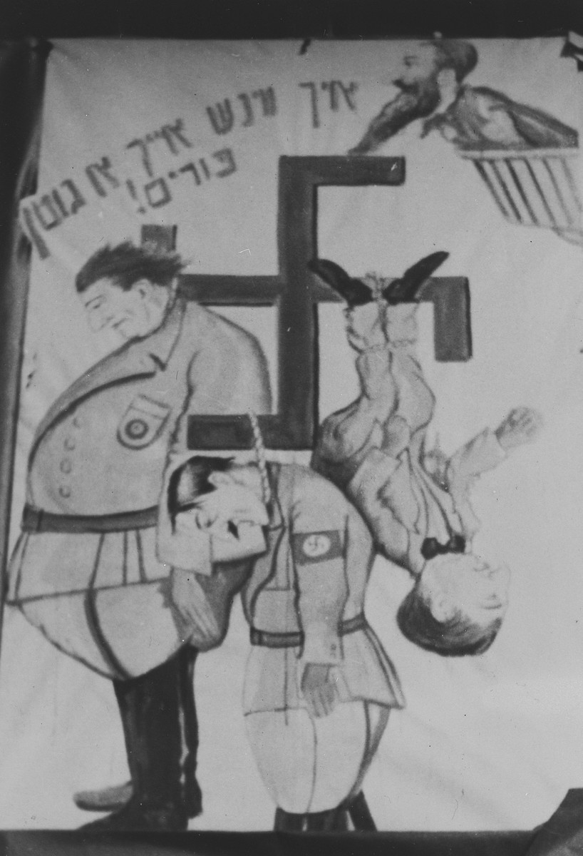 "Photograph of a poster in the Landsberg DP camp with a cartoon illustration of Hitler, Goering and possibly Goebbels hanging from a swastika.  Tha caption reads, ""I wish you a good Purim."""