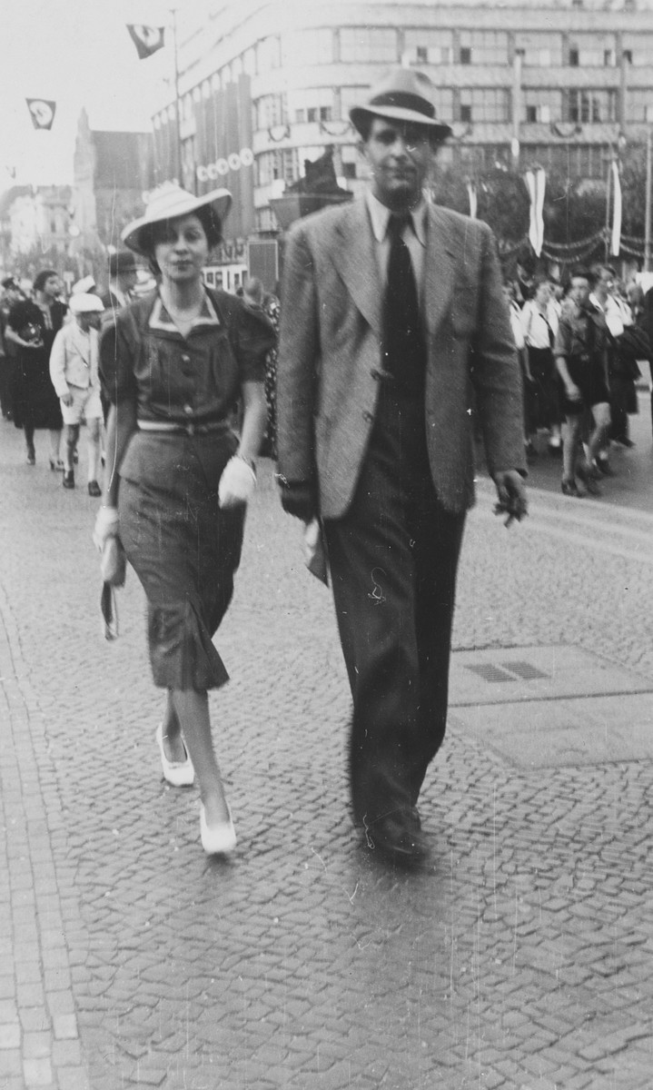 A well-dressed Jewish couple walks down a street in Vienna past a parade of Hitler Youth and hanging swastika flags.  Pictured are Henry (Heinz) and Harriet (Peppi) Fink.