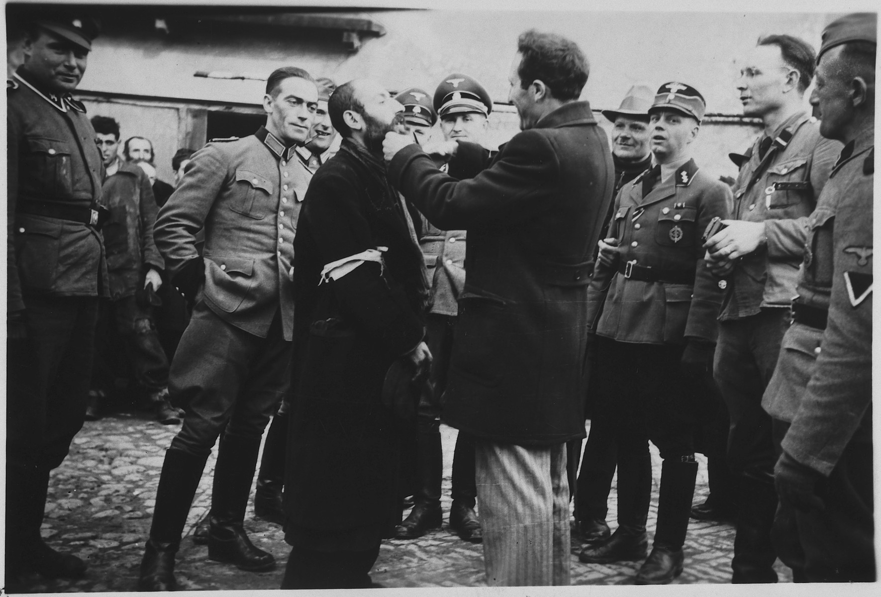 "A Jewish man is forced to shave the beard of a religious Jew while SS men watch in amusement..   The caption of the SS-Archiv says ""Reinrassige Juden angetreten zur Schoenheitspflege in Palinin (?)  Sept. 1941"" (Purebred Jews took up beauty care in Palinin (?) Sept. 1941)."