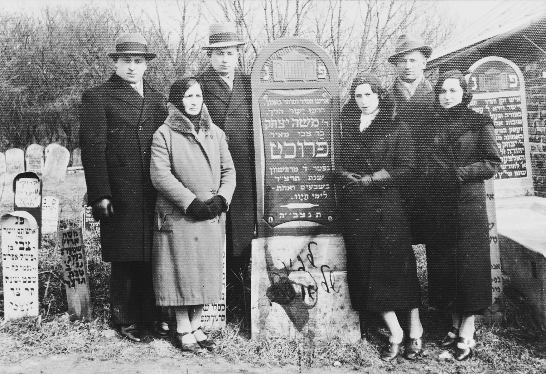 A Polish-Jewish family poses by the grave of its father, Moshe Itzchak Frucht.  Pictured from left to right are Szyja Frucht, Malka Frucht, Avigdor Frucht, Bela and Issac Perec, and Frieda Frucht.