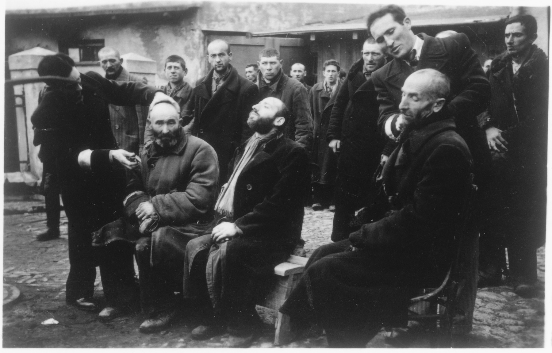 """Jewish men are forced to shave the beards of other religious Jews while SS men watch in amusement.  The caption of the SS-Archiv says """"Reinrassige Juden bei Schoenheitspflege in Palinin (?) Okt. 1941"""" (Purebred Jews during beauty care in Palinin (?) Oct. 1941)."""
