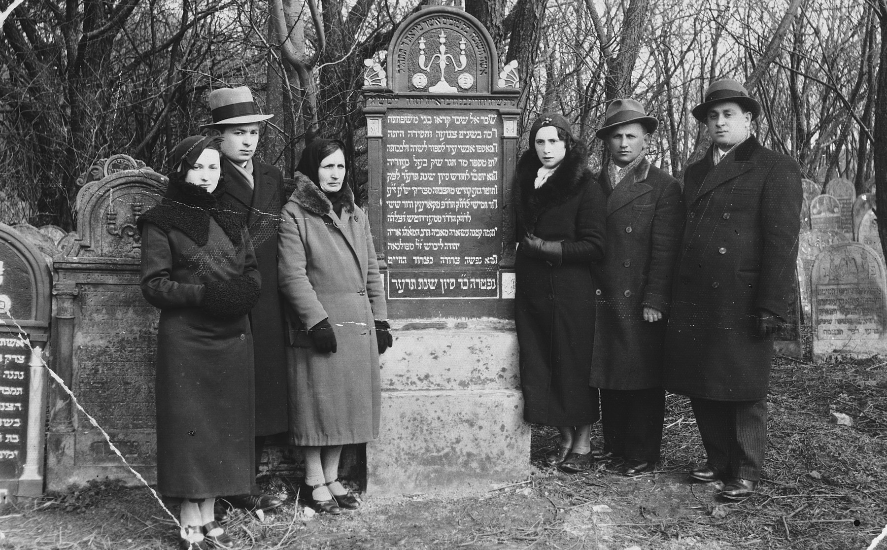 A Polish-Jewish family poses by the grave of its mother.  Pictured from left to right are Freda Frucht, Avigdor Frucht, Malka Toren. Bela Perec, Isaac Perec and Szyja Frucht.